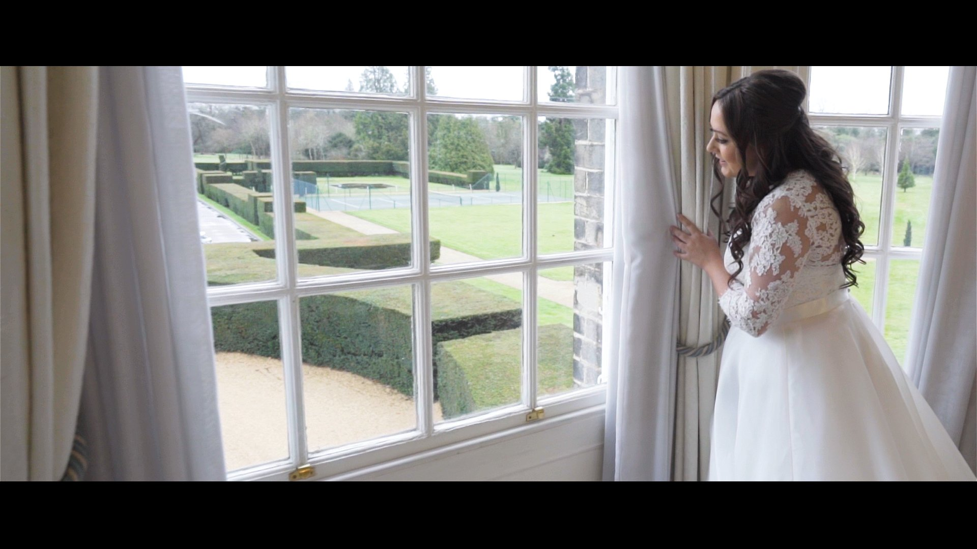 Bride peeks out of window Alex Amy wedding film Hedsor House