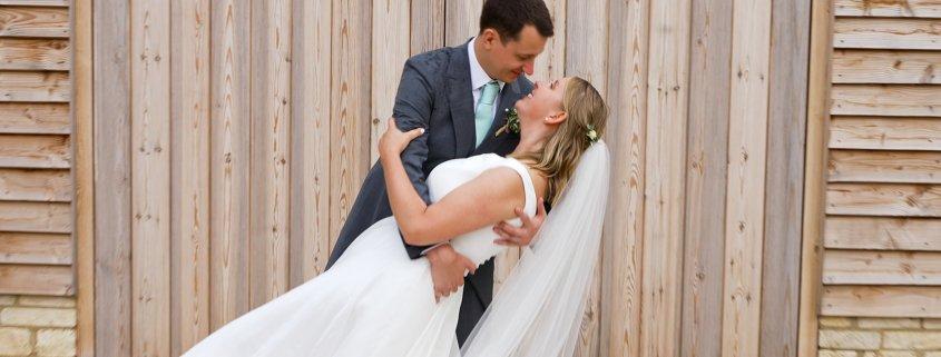 Bride Groom lent other kiss in fron wood doors